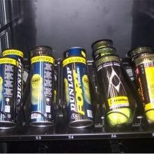 Detalle de los botes de pelotas en una bandeja de la maquina adaptada para la venta de productos deportivos